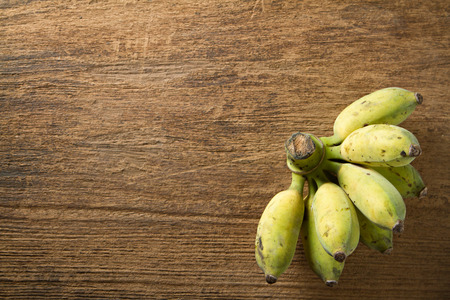 high calorie: Cultivated banana on wooden background. Cultivated banana contain high calorie and Iron useful for healthy.