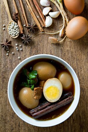 favorite soup: Eggs boiled in the gravy with spices on wooden background. Thai cuisine (Kai pa lo) Stock Photo