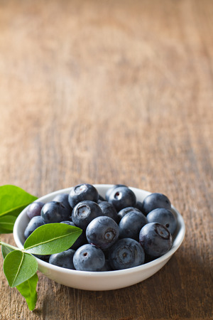 Blueberries in bowl on wooden. Blueberry contain antioxidant organic  useful healthy and nutrition. Banco de Imagens