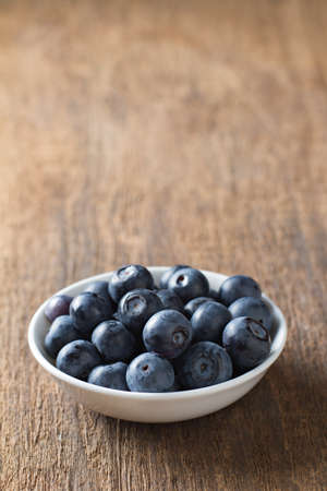Blueberries in bowl on wooden. Blueberry contain antioxidant organic  useful healthy and nutrition. Zdjęcie Seryjne
