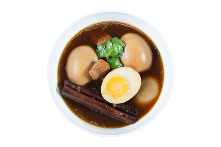 favorite soup: Eggs boiled in the gravy with spices isolated on white. Thai cuisine Kai pa lo Stock Photo