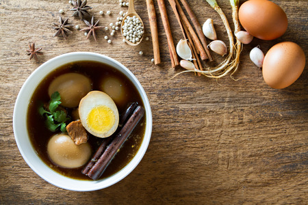 Eggs boiled in the gravy with spices on wooden background. Thai cuisine Kai pa lo