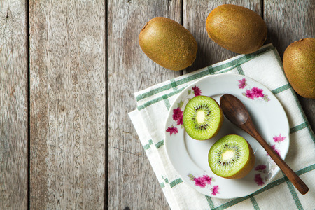 KIwi fruit on dish and spoon on wooden background. Stock Photo