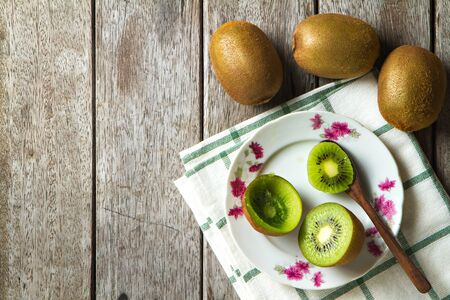 KIwi fruit on dish and spoon on wooden background. Stock Photo
