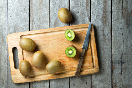 KIwi fruit on cutting board and knife on wooden background.