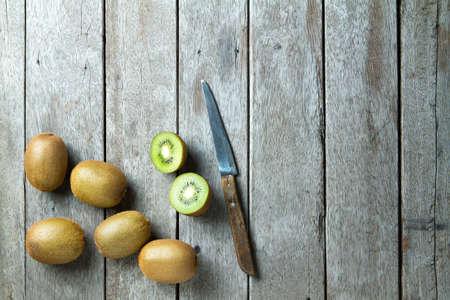 KIwi fruit and  knife on wooden background.