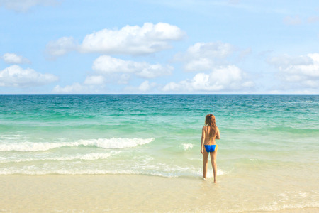 Young woman in bikini walking on the beach. Stock Photo