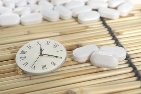 memory drugs: White pill and roman numeric clock on yellow bamboo mat Stock Photo