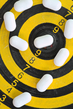 White pills on yellow and black dart target photo