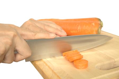 carot: Woman hand slicing carot on wooden chopping block