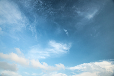 emerge: Abstract white cloud over blue sky background with small dragon head at center emerge from bottom cloud