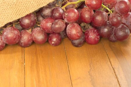Part of branch of red grape pouring out of old agriculture sack on top of wooden table with hugh negative space for usage photo