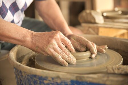 shaping: Old Thai male hand shaping a dish from gray color clay. Stock Photo
