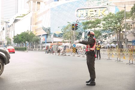 redirect: Bangkok, Thailand - January 14, 2015 Traffic police redirect car out of Pathumwan intersection during Discover Thainess 2015 parade event with MBK shopping center in background Editorial
