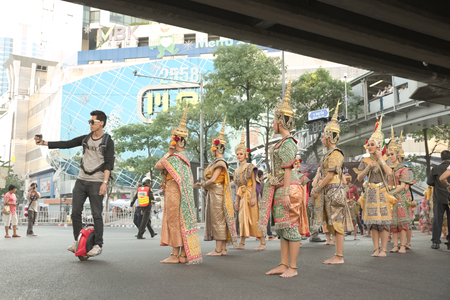 discover: Bangkok, Thailand - January 14, 2015 Man riding unicycle taking selfie with Group of Thai traditional dancers within Discover Thainess 2015 parade event at Pathumwan intersection