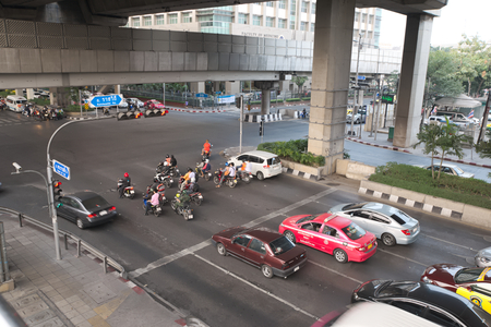 enforce: Bangkok, Thailand - January 30, 2015 :  Various vehicles break law by stop car beyond the white line on the ground during red light. This is typical behavior of people when traffic police is not strictly enforce the law Editorial