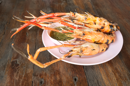 rosenbergii: Bunch of cooked giant freshwater pawn with Thai style spicy sauce over pink dish on top of wooden table