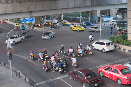 strictly: Bangkok, Thailand - January 30, 2015 :  Various vehicles break law by stop car beyond the white line on the ground during red light. This is typical behavior of people when traffic police is not strictly enforce the law Editorial