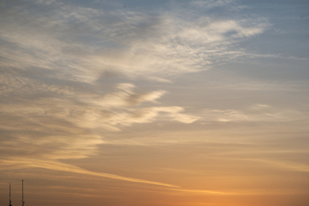 nebulosity: Abstract busy white cloud over clear yellow and blue sky background Stock Photo