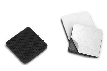 one sheet: Anti scratch and slip rubbers with builtin adhesive over white background with one piece showing adhesive by peeling thin white sheet