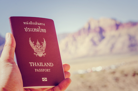 rock canyon: Man holding Thai passport on red rock canyon background Stock Photo