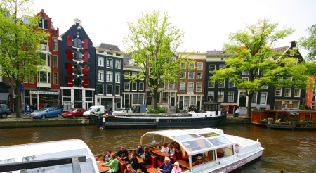 Taxi boat along Amsterdam canal with lovely old house in the background