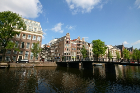 Amsterdam old house with canal as foreground in sunny day photo