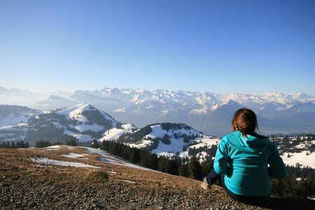 Young woman sitting on the ground of Rigi mountain and looking to Alps photo