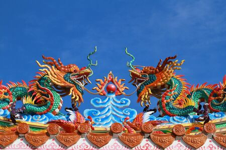 Closed up of twin dragons statue on the roof of Chinese temple