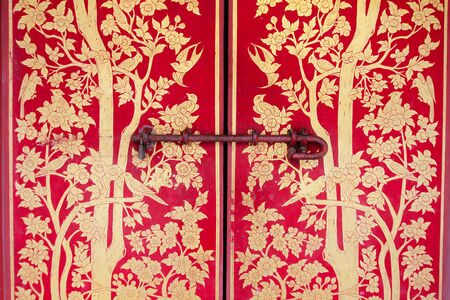 Old gold painting on red door Stock Photo