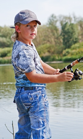 boy fishing with a rod on a vacation photo