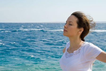 viento soplando: Joven mujer con los brazos a lado y el viento soplando a trav�s de sus pelos. Foto de archivo