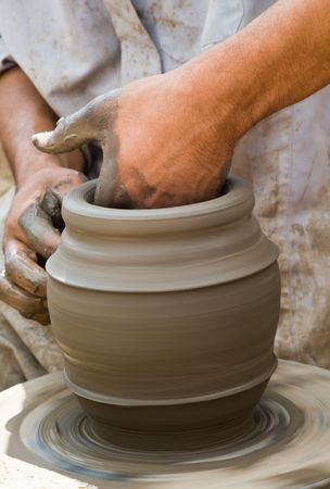 Close-up of potter turning a pot on a potters wheel