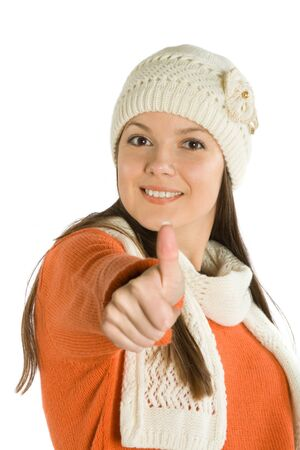 Young woman in cap and scarf giving the thumbs up sign. Isolated on white background photo