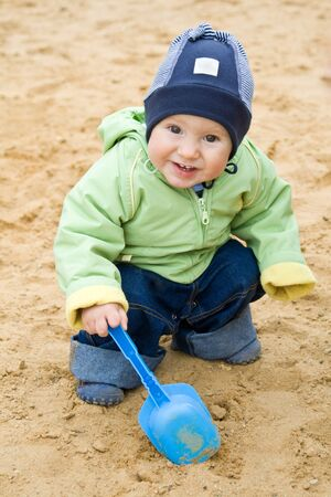 Child with a blue scoop in a sandbox photo