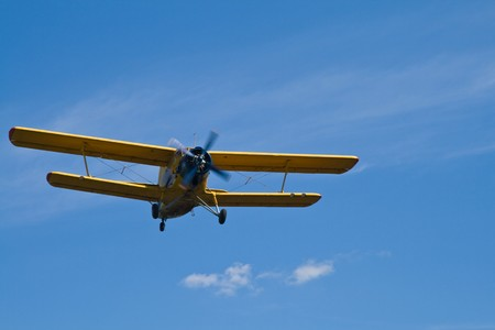 Low flying yellow biplane on blue sky Stock Photo - 3990452