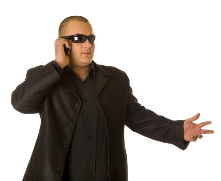 Man in black suit in sun glasses talking on the mobile phone. Isolated on white background photo