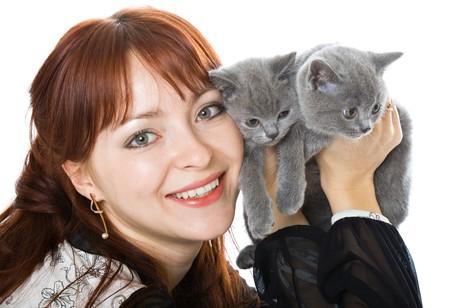 De jonge mooie vrouw en twee kittens. Geïsoleerd op witte achtergrond