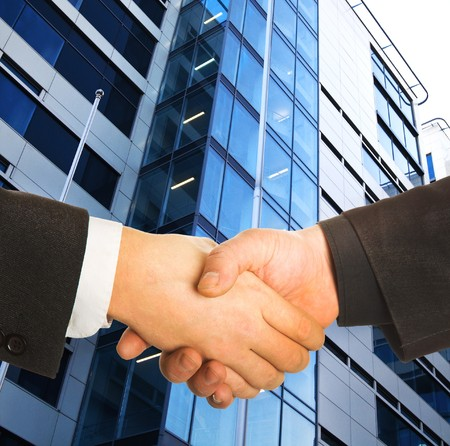 A business handshake in front of a building. photo