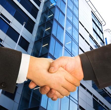manos estrechadas: Una empresa de manos delante de un edificio.
