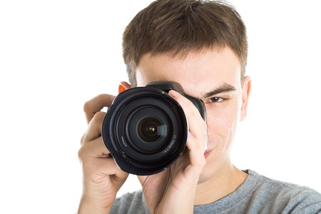 Young photographer with camera. Isolated on white background photo
