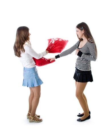 Two happy girlfriends fighting a pillows isolated on white background Stock Photo - 4540821