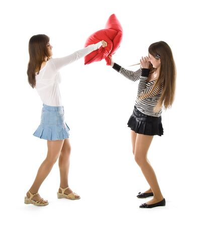 Pillow fight: Two happy girlfriends fighting a pillows. Isolated on white background