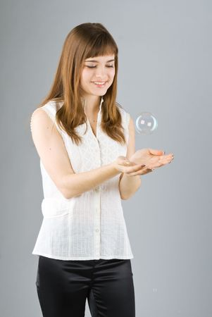 Young beautiful girl catch soap bubble on gray background Stock Photo - 4702467