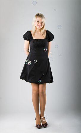 blow out: Giovani bella ragazza colpo di bolle di sapone su sfondo grigio