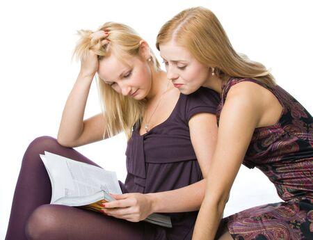 Two girls reading magazine. Isolated on white background photo