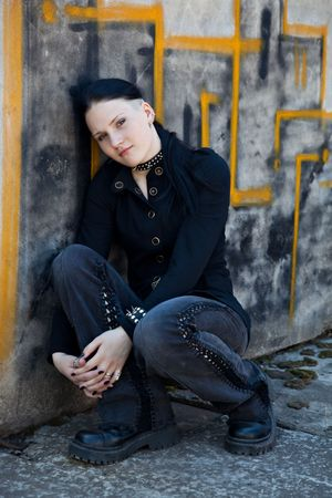 informal clothing: Young girl in black sitting in front of graffiti wall Stock Photo