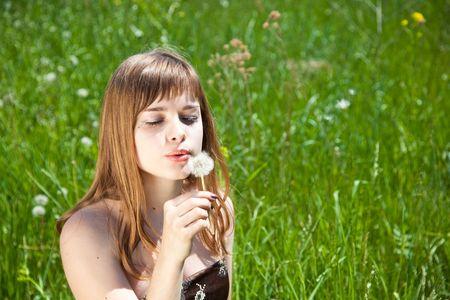 Young beautiful girl blowing on � dandelion photo