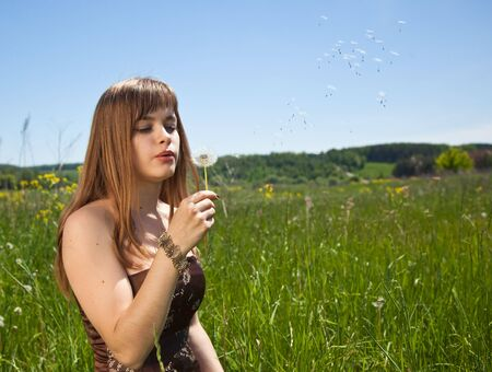 Young beautiful girl blowing on � dandelion photo