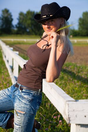 cute young farm girl: Young cowgirl sitting on a white fence